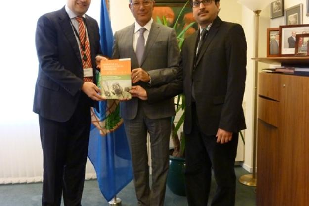 Marc-Michael Blum (left) and R.V.S. Murty Mamidanna (right), Senior Analytical Chemists in the OPCW Laboratory, present a copy of the special edition of Analytical & Bioanalytical Chemistry to OPCW Director-General Ahmet Üzümcü (center).